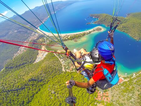 Mugla, Fethiye, Turkey June 15, 2019: Extreme sport. Landscape. Paragliding in the sky. Paraglider tandem flying over the sea in the mountains. Aerial view of paraglider and Blue Lagoon in Oludeniz, Turkey. 免版税图像