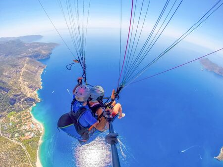 Mugla, Fethiye, Turkey June 15, 2019: Extreme sport. Landscape. Paragliding in the sky. Paraglider tandem flying over the sea in the mountains. Aerial view of paraglider and Blue Lagoon in Oludeniz, Turkey. Imagens