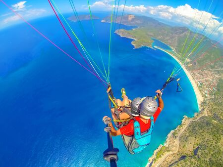 Mugla, Fethiye, Turkey June 15, 2019: Extreme sport. Landscape. Paragliding in the sky. Paraglider tandem flying over the sea in the mountains. Aerial view of paraglider and Blue Lagoon in Oludeniz, Turkey.