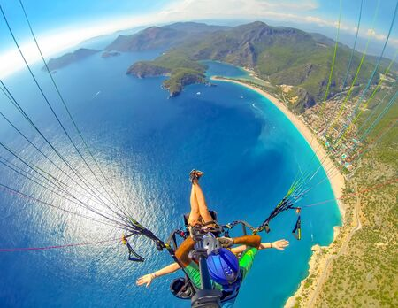 Mugla, Fethiye, Turkey June 15, 2019: Extreme sport. Landscape. Paragliding in the sky. Paraglider tandem flying over the sea in the mountains. Aerial view of paraglider and Blue Lagoon in Oludeniz, Turkey. 版權商用圖片