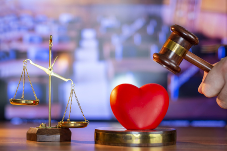 Gavel and red heart on background.law concept