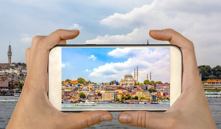 Travel concept - tourist taking photo of Golden Horn against Galata tower, Istanbul, on mobile gadget, Turkey Stock Photo