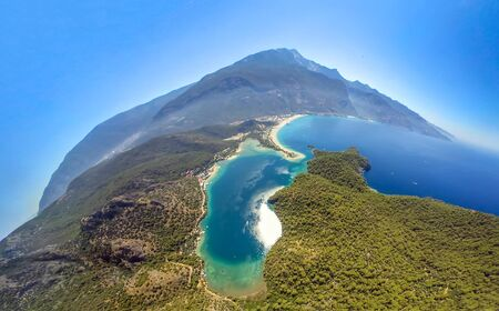 Extreme sport. Landscape. Paragliding in the sky. Paraglider tandem flying over the sea in the mountains. Aerial view of paraglider and Blue Lagoon in Oludeniz, Turkey.
