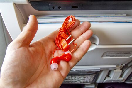 Airplane stereo headphones with two-legged connector placed on folded table