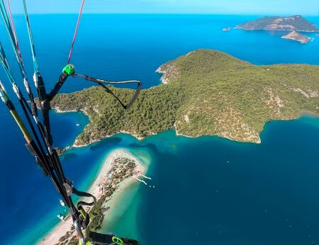 Extreme sport. Landscape. Paragliding in the sky. Paraglider tandem flying over the sea. Blue Lagoon in Oludeniz, Turkey