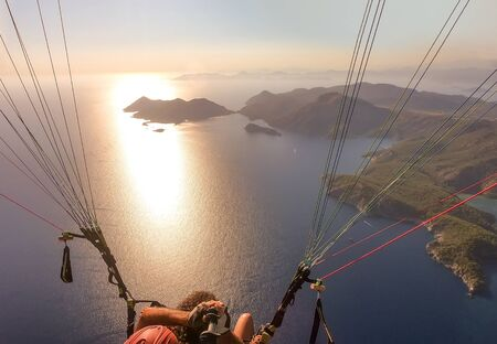 Extreme sport. Landscape. Paragliding in the sky. Paraglider tandem flying over the sea. in Oludeniz, Turkey Zdjęcie Seryjne