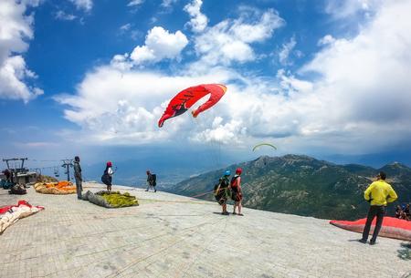 Mugla, Fethiye, Turkey June 15, 2019: Extreme sport. Landscape. Paragliding in the sky. Paraglider tandem flying over the sea. Blue Lagoon in Oludeniz, Turkey Editorial