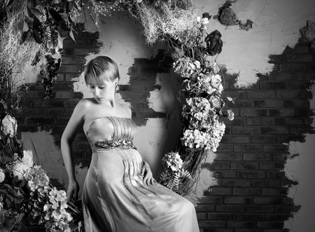 Black and white photo of a sitting pregnant woman in flower decorations