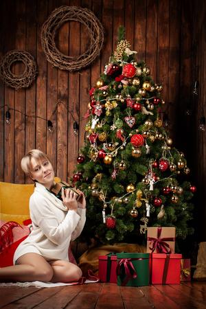 Beautiful woman wearing a warm sweater and socks, sitting on the floor near the Christmas tree 版權商用圖片