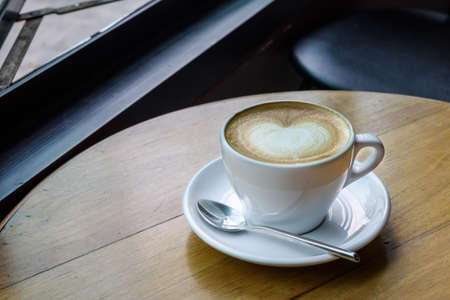 capucinno: Cup of hot latte art coffee on wooden table Stock Photo