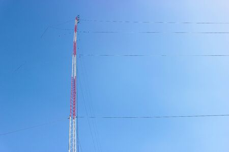 High Red Antenna Tower with Clear Blue Sky Background, Communication Tower Background with Copy Space