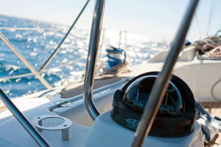 Zeiljacht kompas. Zonnige dag, hemelsblauwe zee water met reflecties. zonder mensen.