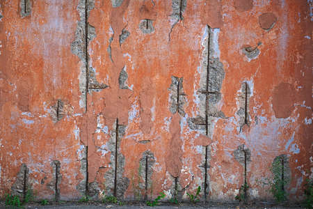 Colorful textured part of the old wall with potholes and pieces of reinforcement Stock Photo