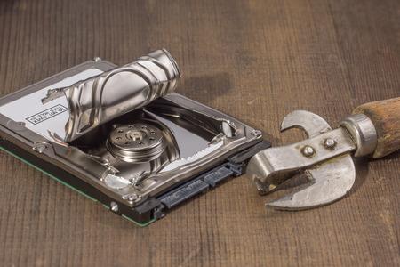 disco duro: el disco duro abierto un abrelatas, sobre una mesa de madera