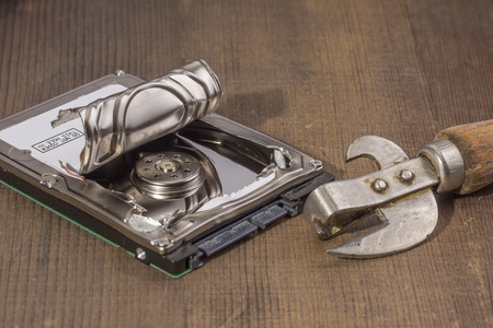 can opener: the opened hard drive a can opener, on a wooden table Stock Photo