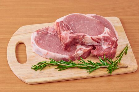 flesh eating animal: pork stake, pieces of crude meat prepared for preparation with greens Stock Photo