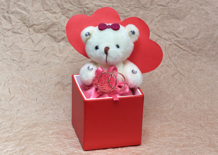 small toy a bear keeps wedding rings in a red box a gift for St. Valentine's Day
