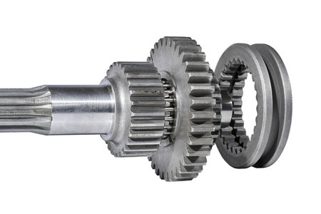 tractor spare parts of a gear wheel on a shaft, are removed on a white background Stockfoto
