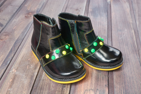 children's boots of black color on a wooden table