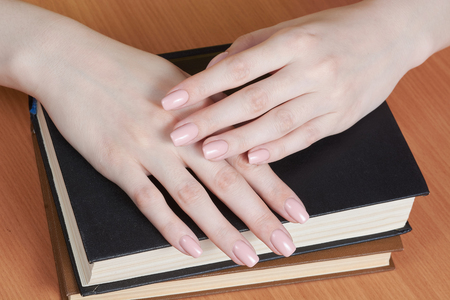 hands on books with manicure of color of tone of skin Stockfoto