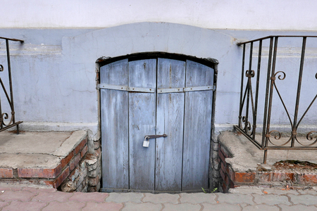the old wooden door to the cellar a door, blue color, is closed on the padlock