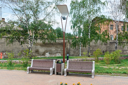 two wooden benches under a lamp in the small square Stockfoto