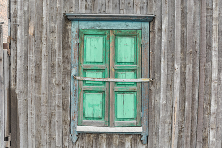 old vintage window closed by a sun blind is painted with green paint against the background of an old wall