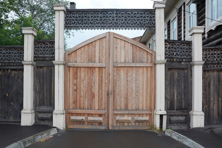 Restored wooden gate in the old fence trimmed with patterns. Stockfoto