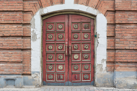 old vintage double-wing doors a main entrance to the brick old building Stockfoto