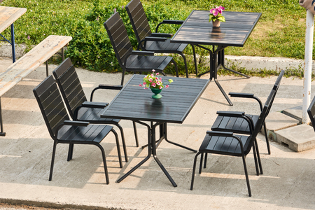 wooden table and chairs of black color of street cafe