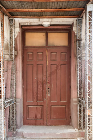 mouldering entrance wooden door of brown color before repair of the building