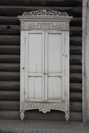 The old window closed by a sun blind in a log house. Trimmed with patterns. Gray color