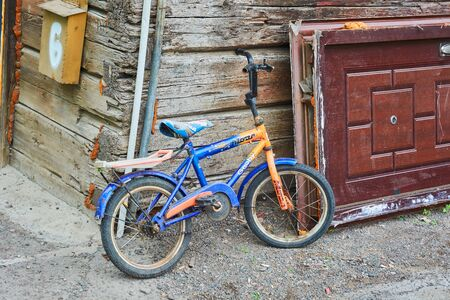 Krasnoyarsk, Russia - July 28, 2018: The old children's  bicycle MODA is abandoned near the old wooden house.