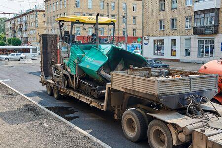 Krasnoyarsk, Russia - July 26, 2018: Transportation of the asphalt spreader to the venue of works.