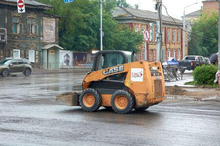 Krasnoyarsk, Russia - July 28, 2018: Pass the loader wheel CASE SV185 leaves the venue of works: restoration of the sidewalk. End of a shift.