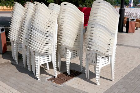 Plastic chairs stacked for loading and transportation, whote color