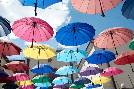 Many colored umbrella suspended on rope between buildings