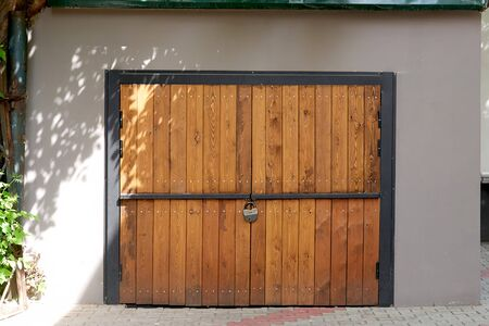 Wooden garage gate yellow, closed on lock Stockfoto