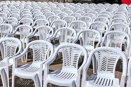 Chairs plastic set in rows for theatrical performance on the square, for the audience, white color