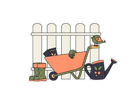 Garden wheelbarrow next to the fence and garden accessories. Concept. Garden supplies. Watering can next to the wheelbarrow and rubber boots.