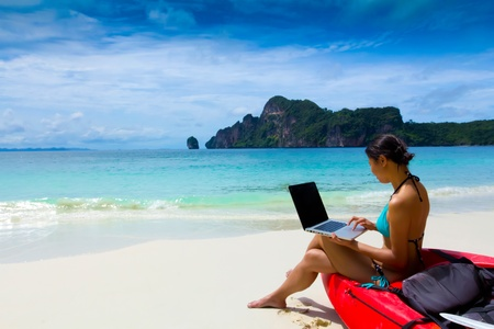 Frau im Bikini mit Laptop am Strand nach dem Sommer Kajak, Krabi, Thailand