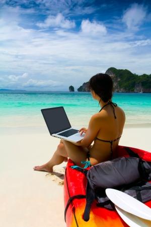 vrouw in bikini met behulp van laptop op het strand na de zomer kajakken, Krabi, Thailand