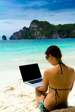 Sexy beautiful woman with sunglasses in bikini using laptop at the the summer beach