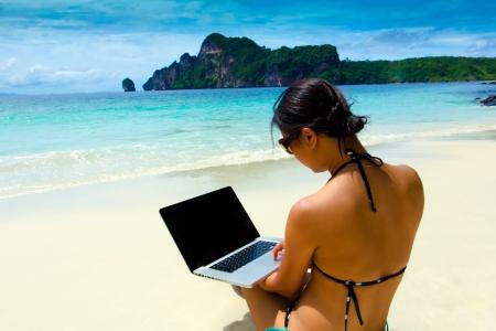 Sexy mooie vrouw met een zonnebril in bikini met behulp van laptop op het strand in de zomer, Krabi, Thailand