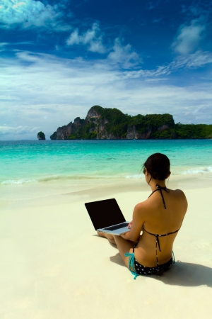 Sexy beautiful woman with sunglasses in bikini using laptop at the the summer beach, Krabi ,Thailand