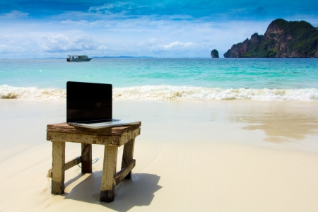 office life: Computer notebook on beach - business travel background, Krabi ,Thailand