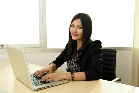 Portret van succesvolle Aziatische zaken vrouw op bureau met laptop Meestal geïsoleerd in het kantoor Stockfoto