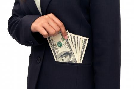 Business-vrouw die dollarbiljetten Amerikaanse bankbiljetten in haar zak op een witte achtergrond