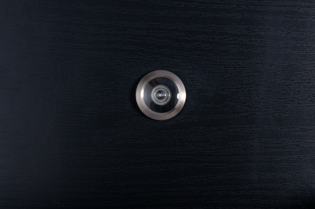 door lens peephole on wooden texture Stock Photo