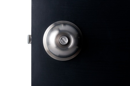 Aluminium door knob on the black door white background. Stock Photo